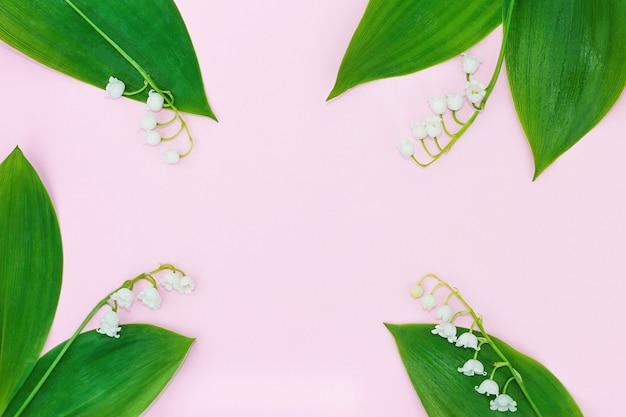 Quatro flores de lírio branco do vale em um fundo rosa formam uma moldura para o texto.