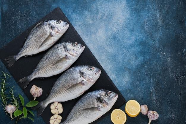 Quatro fresh royal dorades em fundo azul. conceito de comida saudável. vista superior, copie o espaço. mediterrâneo