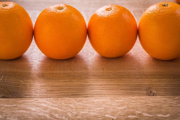 Quatro frutas laranja organizadas em linha na placa de madeira
