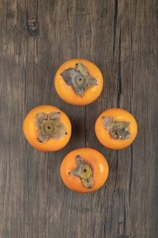 Quatro frutas maduras de caqui colocadas em superfície de madeira