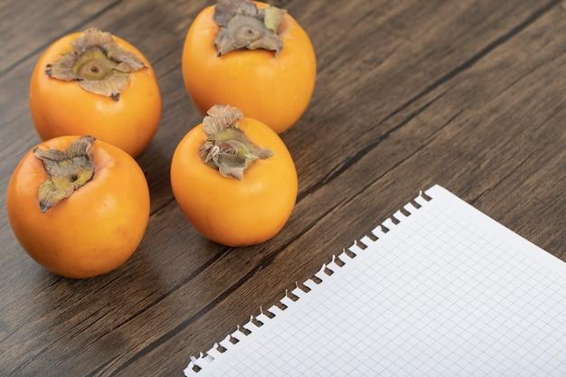 Quatro frutas maduras de caqui e um caderno vazio na superfície de madeira