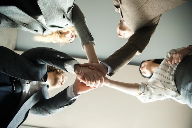 Quatro funcionários de escritório estão juntando as mãos