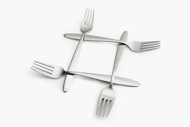Quatro garfos de prata entrelaçados em branco