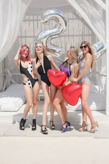 Quatro garotas atraentes descansando no bar da praia, bebem um coquetel refrescante, rindo e se divertindo. os trajes de banho brilhantes e os óculos de sol.