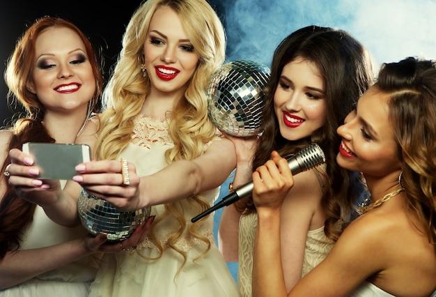 Quatro garotas lindas e elegantes cantando karaokê no clube