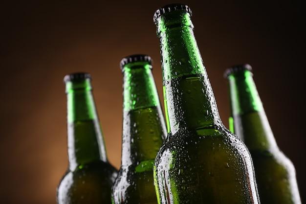 Quatro garrafas de cerveja de vidro verde em fundo escuro iluminado, close-up