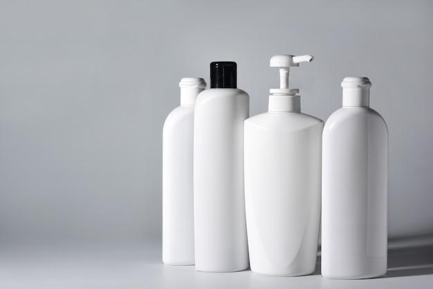 Quatro garrafas de plástico brancas com shampoos e condicionadores de cabelo em um fundo branco.