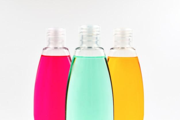 Quatro garrafas de plástico com sabonete líquido amarelo, verde e vermelho.