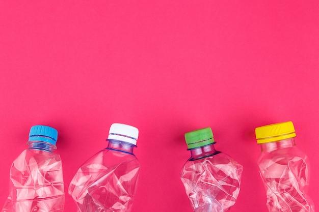 Quatro garrafas pet esmagadas e bonés coloridos closeup em fundo rosa vívido, com espaço para texto