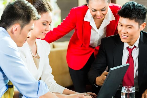 Quatro homens e mulheres de negócios asiáticos chineses se reunindo no saguão de um hotel, olhando documentos em um laptop e bebendo café