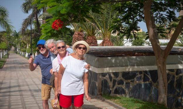 Quatro idosos curtindo um dia de sol nas férias brincando no parque público