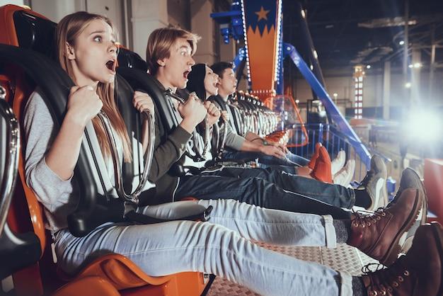 Quatro jovens amigos gritando no parque de diversões.