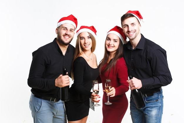 Quatro jovens bonitos em chapéus vermelhos de papai noel segurando taças de champanhe no fundo branco, eles estão felizes e sorridentes