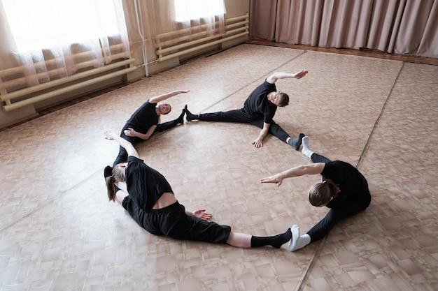 Quatro jovens dançarinos flexíveis em roupas esportivas sentados com as pernas estendidas durante o treinamento no chão do estúdio de dança moderna