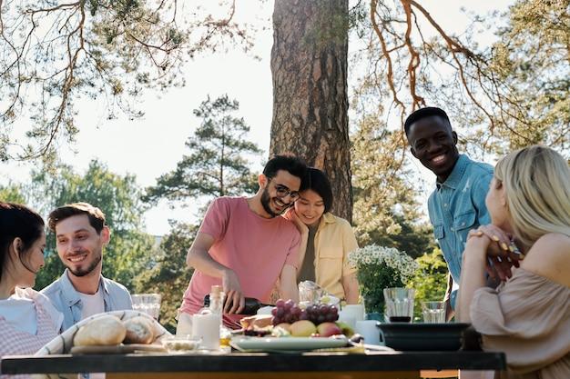 Quatro jovens encontros alegres se olhando com sorrisos e conversando na mesa servida enquanto outro casal vai beber vinho