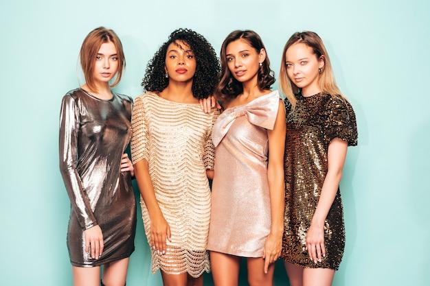 Quatro jovens internacionais lindas mulheres morenas em um vestido brilhante de verão na moda.