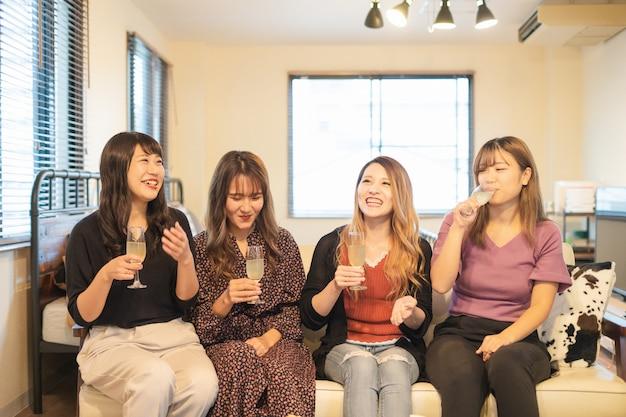 Quatro jovens mulheres asiáticas brindando com taças de champanhe na festa indoor