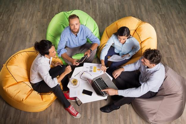 Quatro jovens parceiros de negócio reunião na tabela do café