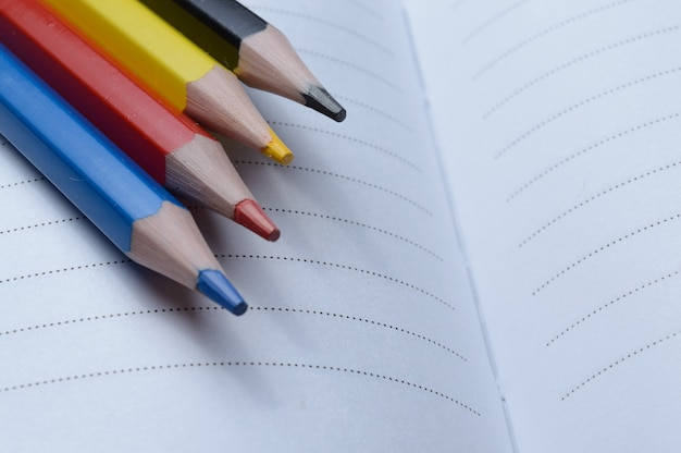 Quatro lápis multicoloridos - azul, vermelho, amarelo, preto. deitar em um caderno aberto.