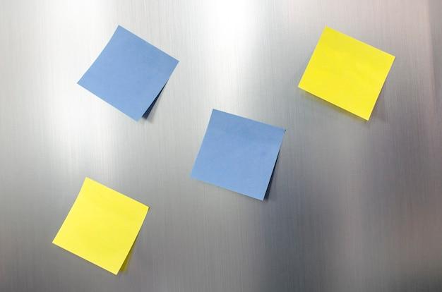 Quatro lembretes de notas adesivas em branco em uma geladeira de aço inoxidável.