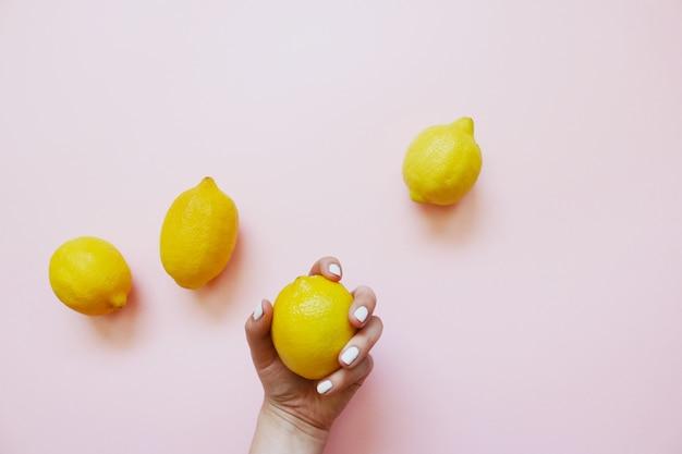 Quatro limões amarelos em um fundo rosa