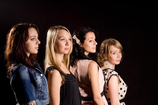 Quatro lindas garotas elegantes paradas atrás umas das outras com as cabeças voltadas para trás
