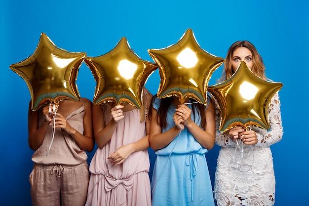 Quatro lindas meninas descansando na festa sobre parede azul