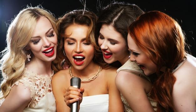 Quatro lindas meninas elegantes cantando karaokê