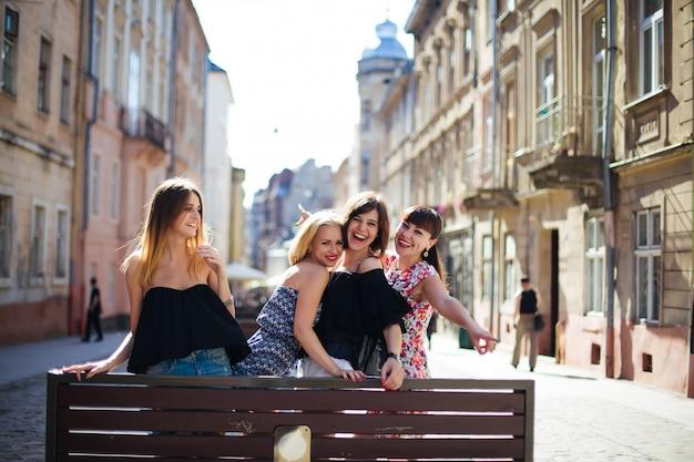 Quatro lindas meninas posando em frente na cidade