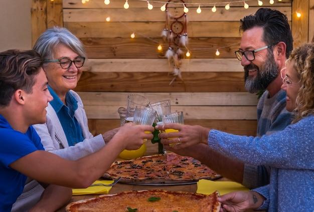 Quatro lindas pessoas dividem uma pizza grande com torradas. adulto com o filho adolescente e a avó