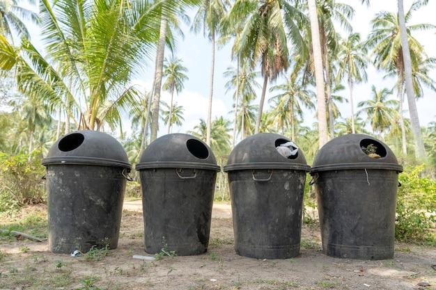 Quatro lixeiras de plástico estão na rua perto de uma praia tropical na ilha de koh phangan, tailândia