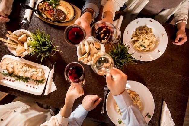 Quatro mãos com vinho tinto, brindando sobre a mesa servida com comida