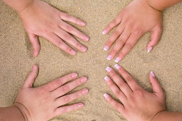 Quatro mãos femininas colocadas na areia da praia.