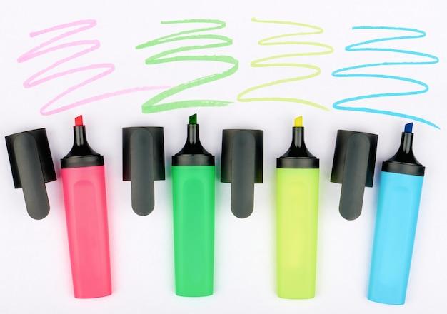 Quatro marcadores coloridos e quatro linhas desenhadas em uma folha de papel branca, close-up, conceito de desenho e trabalho com documentos