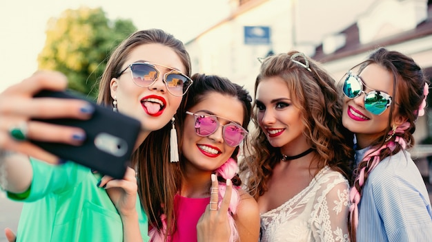 Quatro melhores amigas elegantes e bonitas, posando para selfie, passam um tempo divertido.