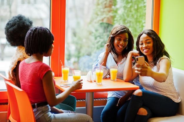 Quatro meninas com sucos sentado e fazendo selfie por telefone