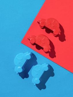 Quatro modelos de carro em uma superfície vermelha e azul