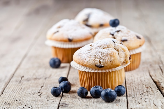 Quatro muffins caseiros frescos com mirtilos na mesa de madeira rústica.