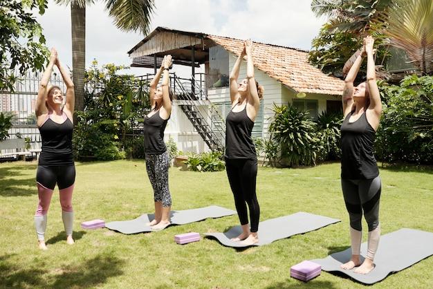 Quatro mulheres praticando ioga ao ar livre, fazendo a pose de saudação ao sol
