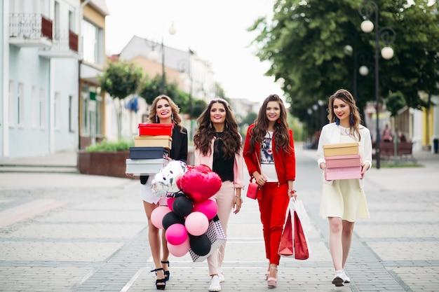 Quatro namoradas na moda com caixas de sapatos na rua.