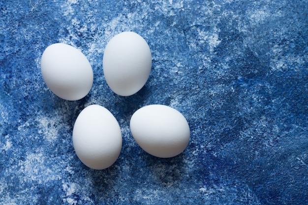Quatro ovos brancos estão sobre uma superfície azul elevada
