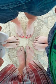 Quatro pares de pernas de pessoas de diferentes idades e sexos foram baleados de cima no verão. talvez a família esteja formando um círculo