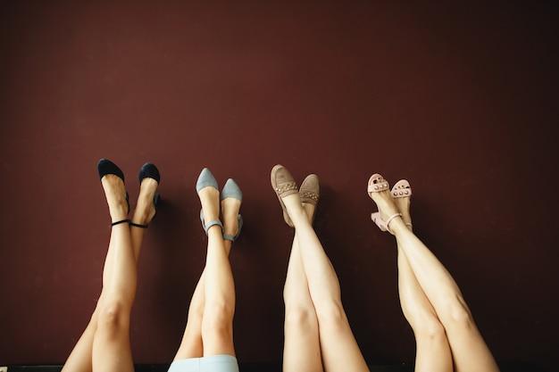 Quatro pares de pernas femininas nos sapatos
