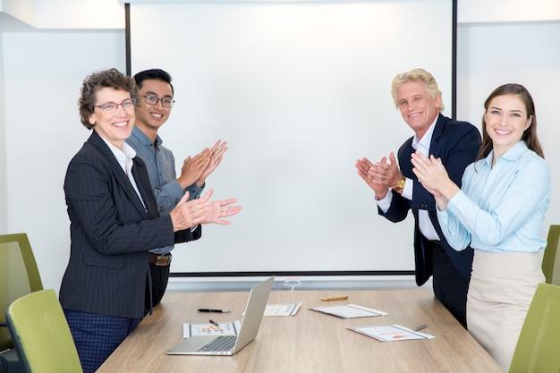 Quatro partners aplaudem na sala de conferências