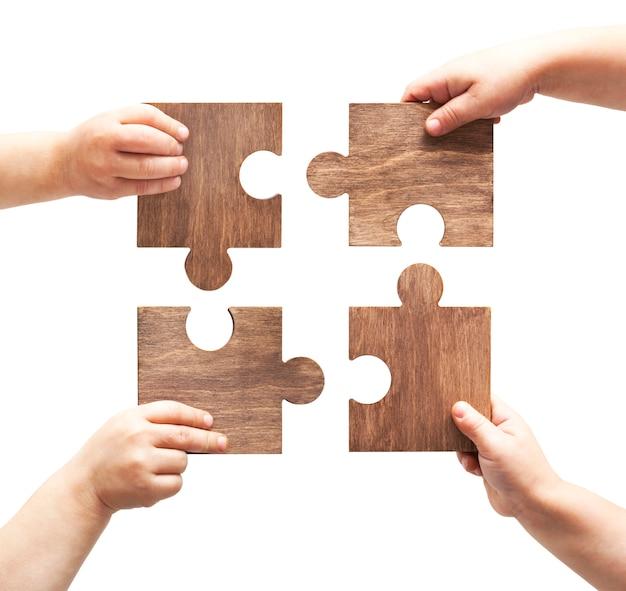 Quatro peças de quebra-cabeças de madeira nas mãos de uma criança