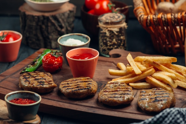 Quatro pedaços de rissóis de bife grelhado com batatas fritas, maionese, ketchup, legumes grelhados