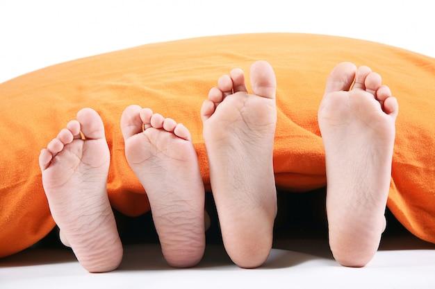 Quatro pés debaixo do cobertor no fundo branco