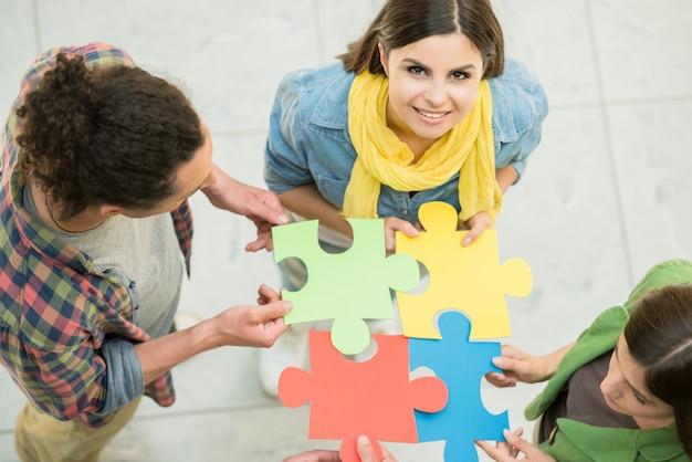 Quatro pessoas criativas tentando conectar peças de quebra-cabeça.