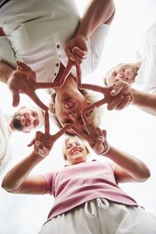 Quatro pessoas dobram as mãos juntas como sinal do trabalho em equipe