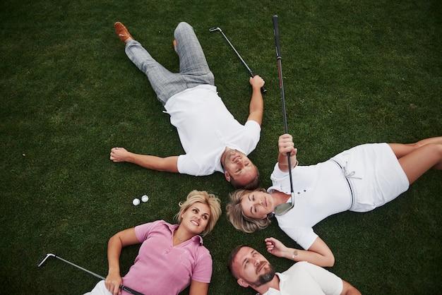 Quatro pessoas, dois homens e duas mulheres, deitam-se no campo de golfe e relaxam após o jogo
